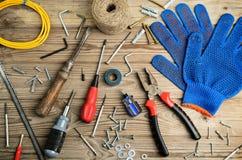 手套和套在水平一张木的桌上的工具 免版税库存照片