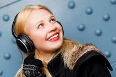 手套和耳机听的音乐的微笑的姜女孩 库存图片