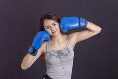 手套微笑的拳击手女孩在灰色T恤杉 免版税库存照片