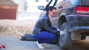 手套的一名妇女与板钳松开坚果在汽车的轮子 影视素材