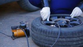 手套的一名妇女从在盘上的一个车胎松开一个盖帽 股票录像