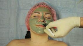 手套的一名美容师应用一个治疗黏土面具于与刷子的一张woman's面孔 影视素材