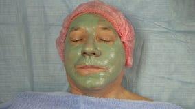 手套的女性美容师应用在一个男性客户的面孔的泥面具 影视素材