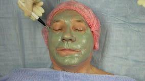 手套的女性美容师应用在一个男性客户的面孔的泥面具 股票视频