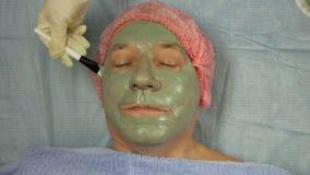 手套的女性美容师应用在一个男性客户的面孔的泥面具 股票录像