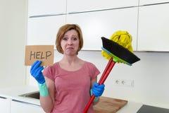 手套的妇女在家厨房与清洁笤帚和拖把请求帮忙 免版税库存图片
