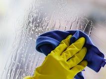 手套的手清洗的窗口旧布和浪花 库存图片