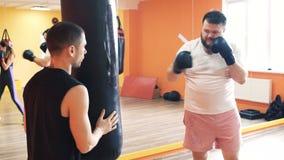手套的肥胖人打在健身房的吊袋 肥满人的各自的减肥钻子 把装箱的训练与 影视素材
