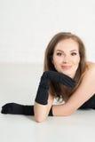 黑手套的高雅在轻的baclground的妇女和礼服 微笑 库存图片