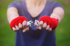 手女孩在拳击绷带断裂滚动了每堆香烟 对一种健康生活方式的Moitvatsiya 反对抽烟的体育 免版税图库摄影