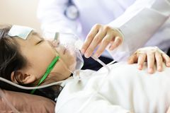 手女性照料者特写镜头拿着与逗人喜爱的儿童患者的氧气面罩在医院病床或家,女孩投入上 免版税库存图片