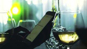 手对在轻的bokeh背景的白葡萄酒的女性用途智能手机和杯 3840x2160 股票录像