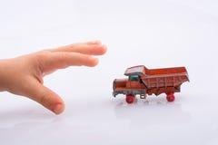 手将劫掠一辆红色玩具卡车 库存照片