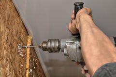 手工作者特写镜头操练有钻子的木墙壁 库存照片