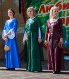 手工制造中世纪的礼服的妇女在现场 免版税库存照片