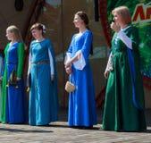 手工制造中世纪的礼服的妇女在现场 免版税库存图片