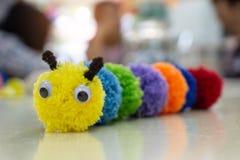 手工制造五颜六色的蠕虫玩偶和被弄脏的背景 库存图片
