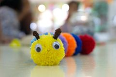 手工制造五颜六色的蠕虫玩偶和被弄脏的背景 免版税库存图片