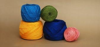 手工制造和爱好供应 钩针编织的五颜六色的毛线和编织在中立或米黄背景 钞票 库存图片