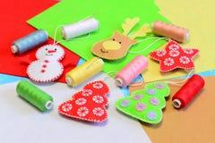 手工制造圣诞树装饰 逗人喜爱的毛毡鹿头,圣诞树,雪人,星装饰,上色了毛毡片断被设置 免版税库存图片