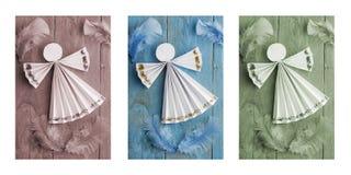 手工制造圣诞节装饰,在木背景的纸天使 三张相联 库存图片
