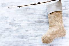 手工制造圣诞节长袜由粗麻布和布料,垂悬的f制成 免版税库存照片