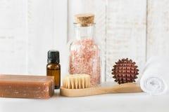 手工制造在白色大理石背景的煤焦油肥皂桃红色喜马拉雅盐精油毛巾刷子凉鞋木按摩球 温泉 库存照片
