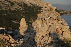 手工制造堆在山的石头在日落期间 免版税库存图片
