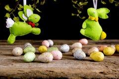 手工制造复活节兔子和鸡蛋在木桌上 黑色背景 免版税库存图片