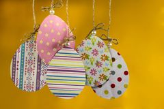 手工制造复活节的背景 小组色的鸡蛋由纸吊制成在绳索在黄色背景 免版税库存照片