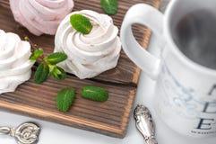 手工制造奶油和草莓蛋白软糖 用薄荷叶装饰 在一个白色杯子的茶有一件蓝色装饰品的 ?? 图库摄影