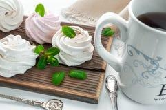 手工制造奶油和草莓蛋白软糖 用薄荷叶装饰 在一个白色杯子的茶有一件蓝色装饰品的 ?? 免版税图库摄影