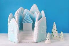 手工制造姜饼喜欢冰宫殿和冷杉木在蓝色背景 库存照片