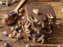 手工制造巧克力和玫瑰用肥皂擦洗棕色木背景 库存照片