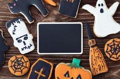手工制造曲奇饼为万圣夜和问候的黑色的盘子 图库摄影