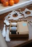 手工制造木圣诞节的装饰 鹿、圣诞树和星的头 在一个盘子的蜜桔在背景中 免版税库存图片