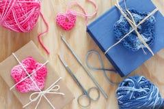 手工制造桃红色,蓝色钩针编织花和心脏在礼物 免版税库存照片