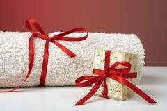 手工制造橄榄色的肥皂和一块毛巾,作为礼物。 库存图片