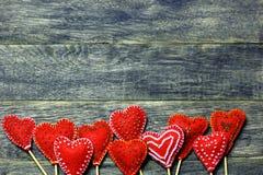 手工制造毛毡红颜色心脏底下框架边界在黑暗的老木背景的 库存照片