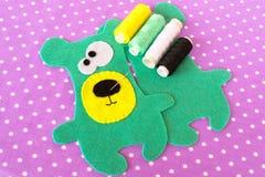 手工制造毛毡绿色熊在与圆点的紫罗兰色背景设置了 如何缝合玩具熊玩具 步骤 库存照片