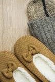 手工制造温暖从粗糙的毛纱蓬松毛皮拖鞋的被编织的袜子在木背景 冬天秋天Eco时尚布料亲属 库存照片