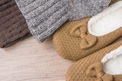 手工制造温暖从粗糙的毛纱蓬松毛皮拖鞋的被编织的袜子在木背景 冬天秋天Eco时尚 库存图片