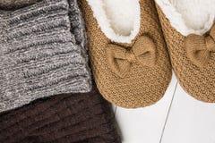 手工制造温暖在白色板条木头背景的被编织的袜子粗砺的毛纱蓬松冷杉拖鞋 冬天秋天Eco时尚亲属 库存图片