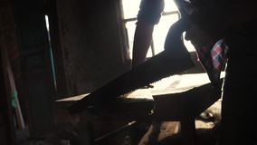 手工制造的木匠和工艺概念慢动作录影 木匠在车间锯的阳光下的锯一棵树从a 股票录像