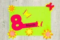 手工制造看板卡的问候 题字3月8日和纸花和蝴蝶  平的位置 库存照片