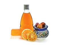 手工制造肥皂、桔黄色阵雨胶凝体瓶和花瓶 在空白背景 图库摄影
