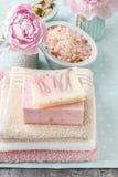 手工制造肥皂、碗海盐和桃红色毛巾两个酒吧  免版税图库摄影