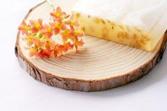 手工制造肥皂和花在木和白色背景 库存照片