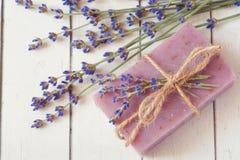 手工制造肥皂酒吧用淡紫色开花在白色木难看的东西背景 免版税库存图片