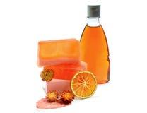 手工制造肥皂,桔黄色阵雨胶凝体瓶 免版税库存照片